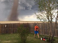 Photo of man casually mowing lawn with tornado on the horizon goes viral