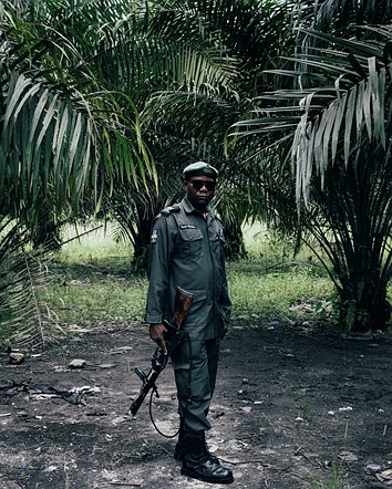 """Category Winner, Professional, Environment: '85 Trader, a Local Policeman in Ughelli, Niger Delta, Nigeria' by <a href=""""http://www.robinhinsch.com/"""" rel=""""noopener"""" target=""""_blank"""">Robin Hinsch</a> (Germany)"""